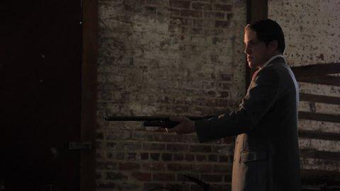 NEW YORK CITY - SEPTEMBER 2013.  Re-enactment, recreation of 1920s, 1930s Gangster/Mobster in Dark warehouse, with shotgun Gun - fires.  Mobster, mob boss during prohibition days. Boardwalk Empire.