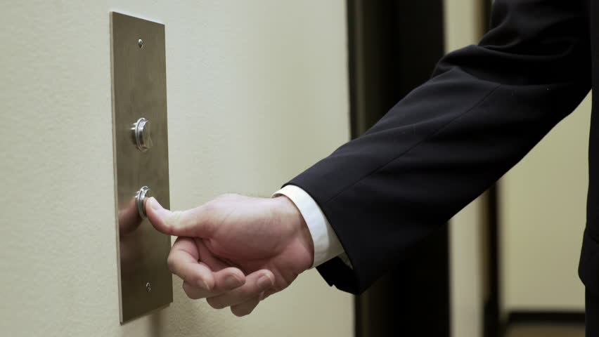 impatient businessman pressing the elevator button and tapping on the wall