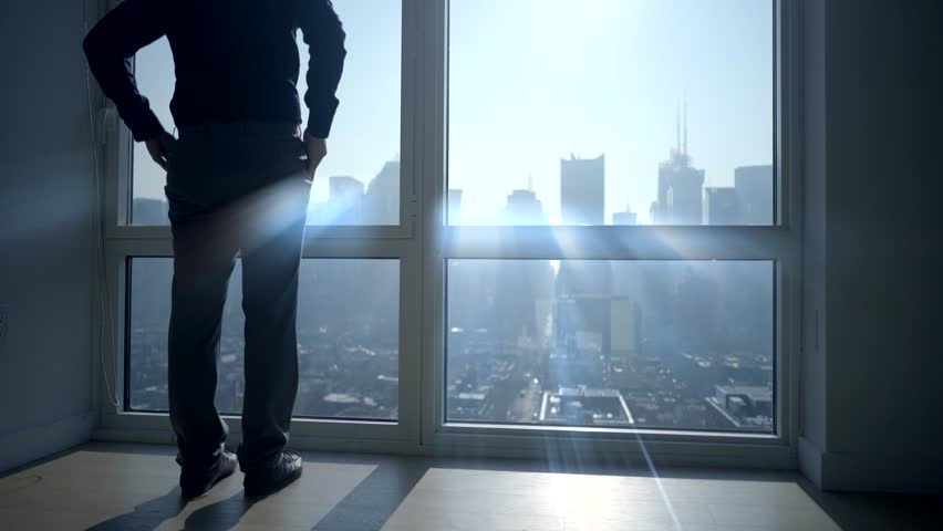 silhouette of man opening roller blinds in the morning starting daily business in city office building. sunlight beams shining through window. urban skyline background