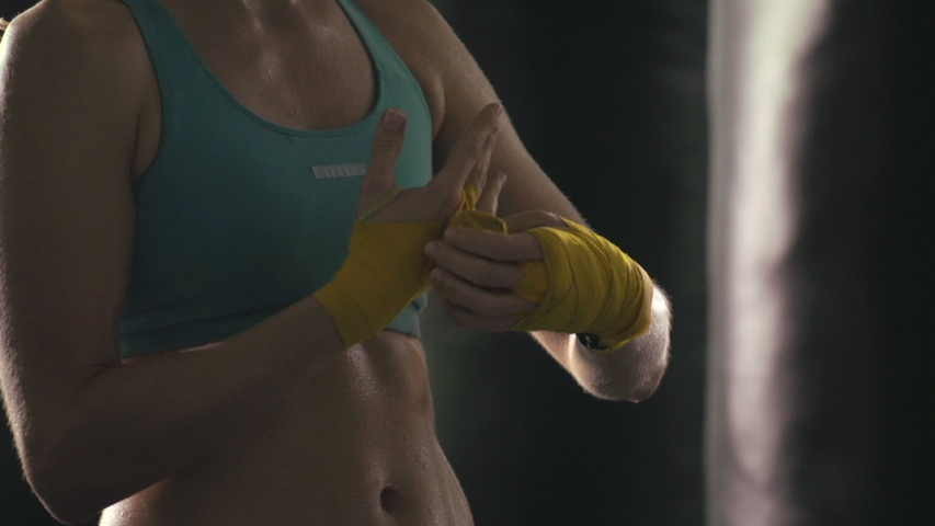 A woman prepares for Muay Thai kickboxing training at the gym. - Slow Motion - Model Released - filmed at 59.94 fps - Clip is HD 1920 x 1080