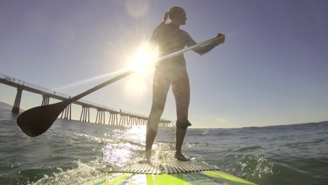 POV of a woman sup stand-up paddleboard surfing at the beach. - Slow Motion - Model Released - filmed at 59.94 fps - Clip is HD 1920 x 1080