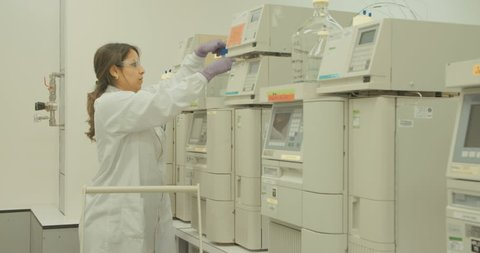 Researcher working with mass spectrometers in a pharmaceutical research lab