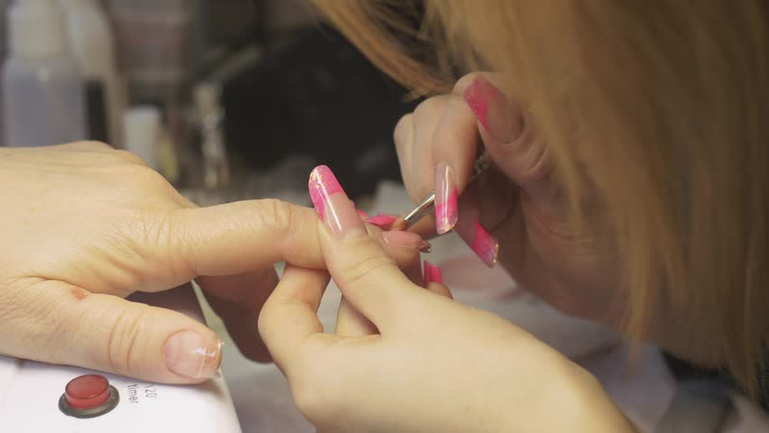 Master apply gel lacquer on nails of client in beauty saloon by brush. Nail extension by gel polish. Close up   Shutterstock HD Video #16428868