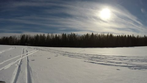 Winter. Speed riding a snowmobile on forest and open countryside.