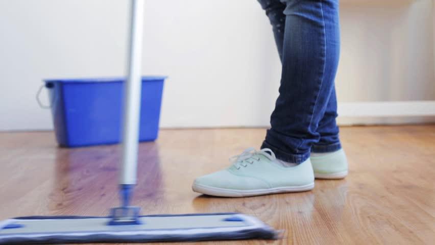 medium panning shot of woman mopping kitchen floor stock footage