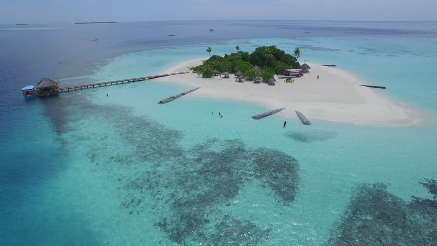 Aerial shot of a small tropical island in Maldives island, 2015. Palms and jetty on the sandbank. | Shutterstock HD Video #16501021