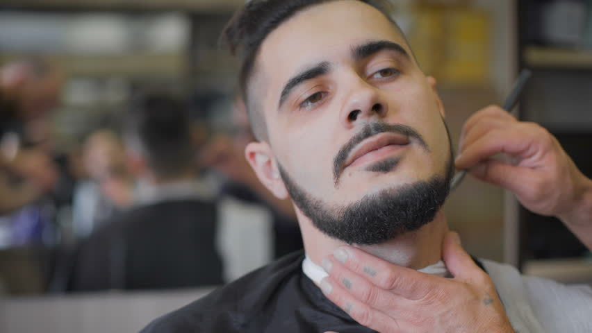 Hipster hairstyles in the salon. Professional barber uses a straight razor to make the beard trend form.  | Shutterstock HD Video #16521808