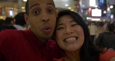 Attractive young Inter racial couple taking selfie Shibuya crossing Hachiko exit Tokyo Japan