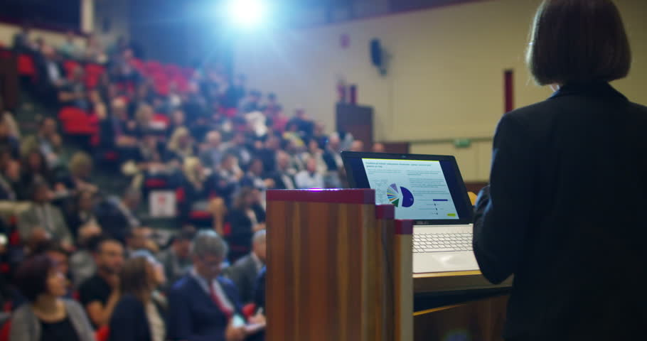 A woman holds a speech to the audience in an auditorium on a convention of economics and finance their business and to applaud his speech