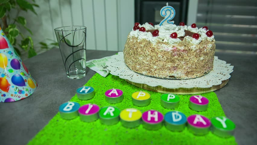 A Delicious Cake Is On The Table For 2 Year Old Boy There Are Colourful Candles With Happy Birthday Letters In Front Of It