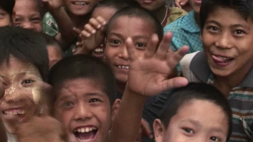 MYANMAR - CIRCA 2009: A crowd of children smile and wave at the camera in Myanmar circa 2009