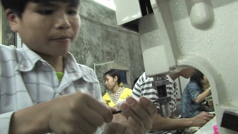 CHINA - CIRCA 2009: A child trying to fix a sewing machine with the help of a wench in a sweatshop in China circa 2009