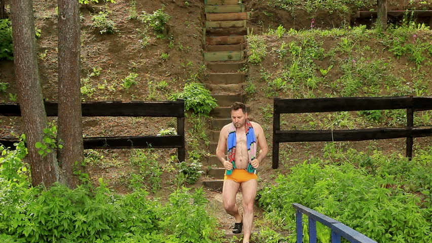 Corpulent and hairy male in swimming trunks walking down the stairs to the lake