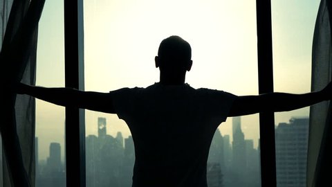 Young man unveil curtains and admire cityscape view, slow motion