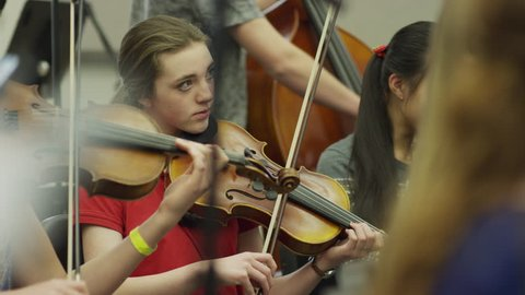 Medium shot of teenage girls playing violins in orchestra practice / American Fork, Utah, United States
