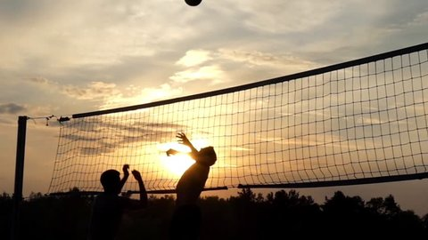 Professional Beach Volleyball at Sunset in Slow Motion. the Action Near the Net - Attacking and Blocking.