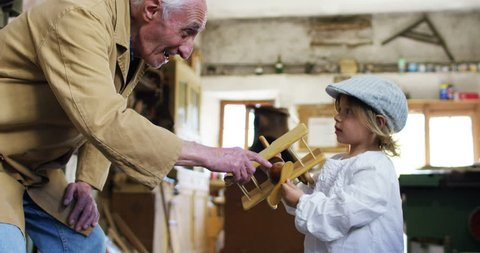 in an old carpentry shop a child and grandfather playing with a wooden airplane concept of tradition that continues over time and surprise