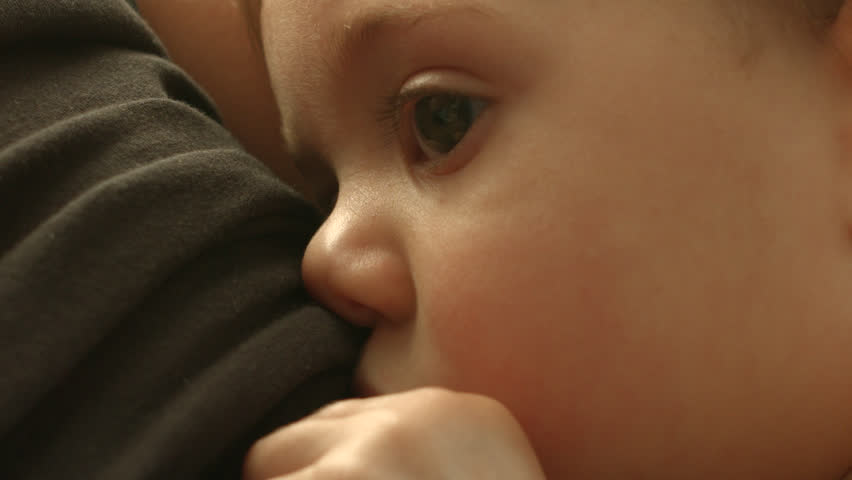 A baby breastfeeding from her mother, close up, drinking milk in slow motion