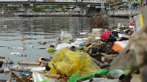 Editorial: Ca Mau, Vietnam, 20th May 2016. Water pollution in Mekong River, plastic bags and other rubbish swimming in the water while a boat is passing.