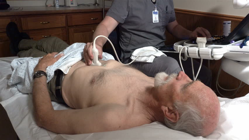 PROVO, UTAH - APRIL 2016: A unidentifiable ultrasound technician preforms a medical abdominal ultrasound procedure on an aging male Medicare patient to check for a descending aortic aneurysm.