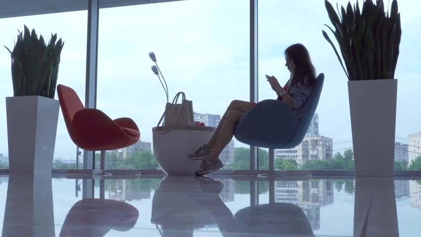 Beautiful young woman sitting and using her smartphone against big window | Shutterstock HD Video #16759018