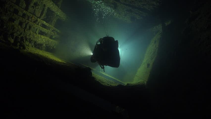 Scuba diver swims inside the shipwreck corridor - Umbria shipwreck, Red sea, Sudan. Diver silhouette at backlight.