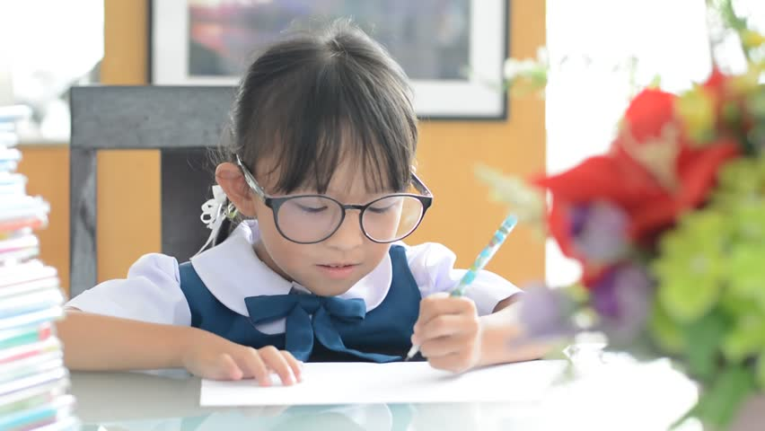 Asian Thai schoolgirl student wearing school uniform writing on a table. | Shutterstock HD Video #16772848