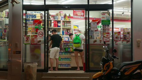 Phuket, Thailand - May 10, 2016: Time Lapse Seven Eleven store building exterior open and closed doors