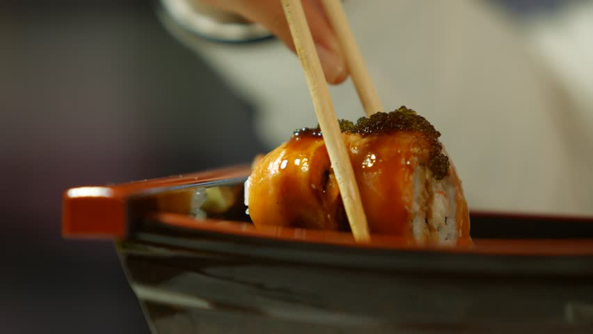 Hand with chopsticks taking sushi. Sushi rolls on dark plate. It's snack time. Getting familiar with japanese cuisine.