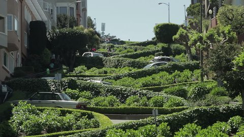 A view of the famous crooked Lombard Street in San Francisco, with cars driving down it. San Francisco, CA - USA: July, 2015