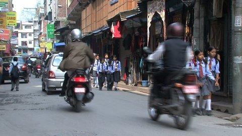 KATHMANDU - CIRCA 2010: People, cars and bikes circulate through the city circa 2010 in Kathmandu.