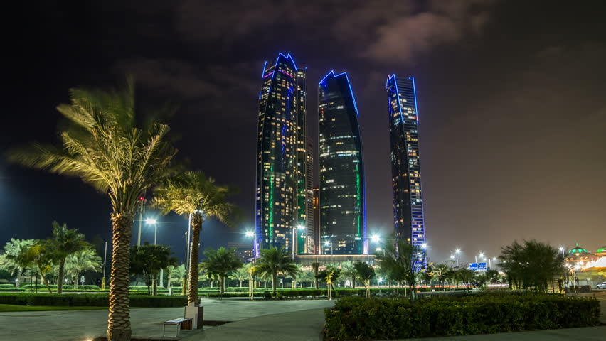 ABU DHABI, UAE - JANUARY 16: Famous towers buildings in Abu Dhabi night timelapse hyperlapse from park with palms. United Arab Emirates. Five towers complex is the third tallest building in Abu Dhabi.