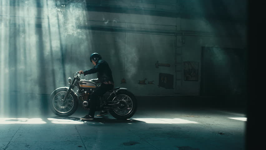 Young thoughtful Caucasian male biker in leather jacket mounts his custom cafe racer motorcycle in large warehouse garage. 60 FPS slow motion Blackmagic URSA Mini RAW graded footage