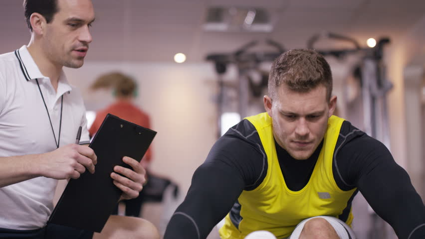 4K Man with prosthetic leg working out at the gym with personal trainer. Shot on RED Epic. UK - April, 2016