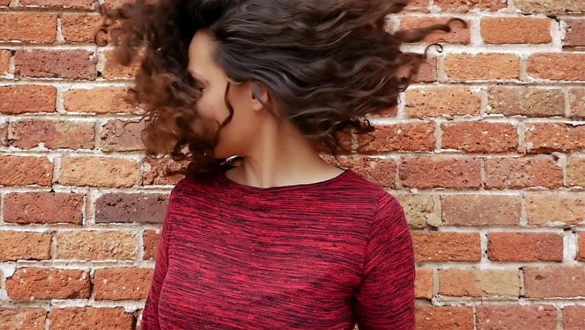 Portrait of happy young woman shaking her beautiful curly hair on brick wall, slow motion