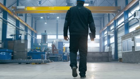 Factory worker in a hard hat is walking through industrial facilities. Shot on RED Cinema Camera.