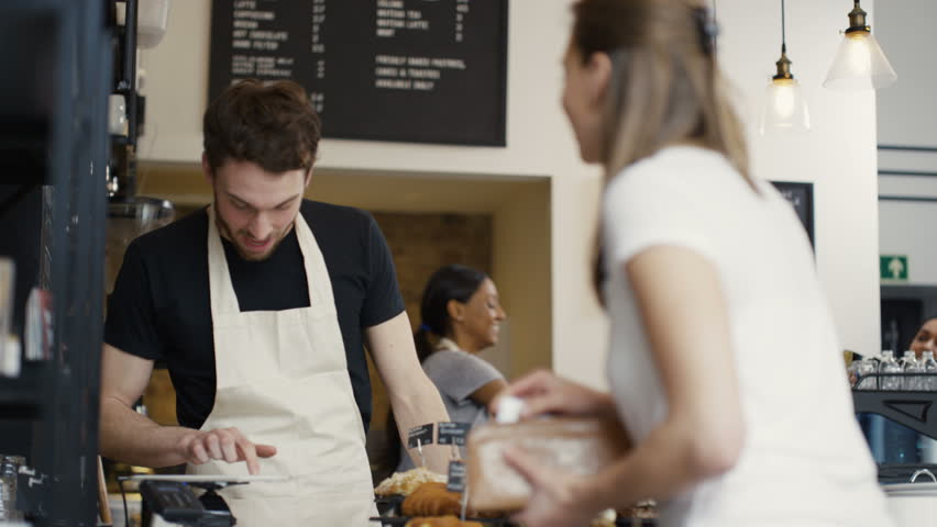 4K Cheerful worker serving customers & taking payment in city coffee shop UK - April, 2016 | Shutterstock HD Video #16996078