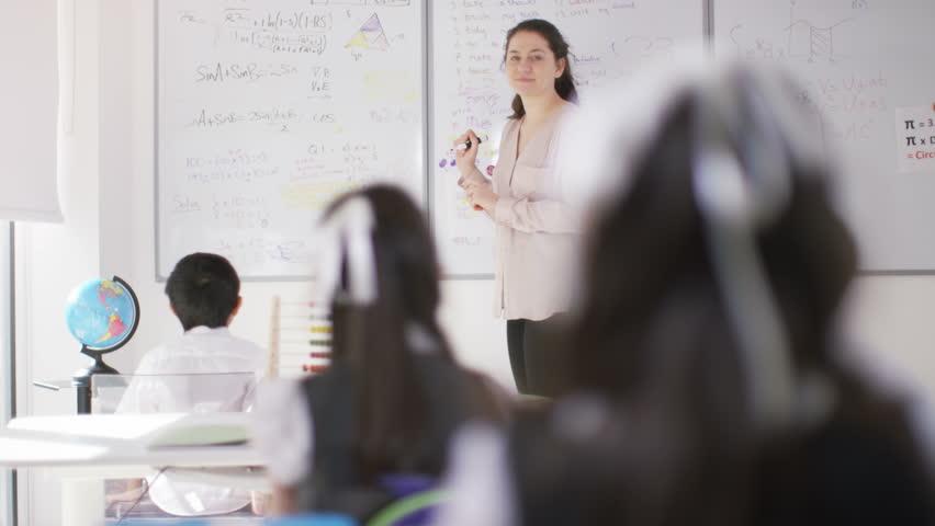 4K Happy school children in class listening to teacher & answering questions UK - April, 2016 | Shutterstock HD Video #16996351