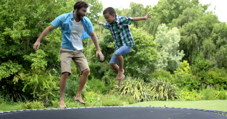 Happy father and son playing on the trampoline in the garden