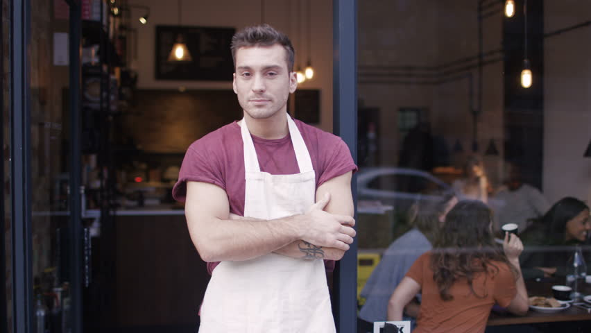4K Happy male business owner standing in the doorway of cafe UK - April, 2016
