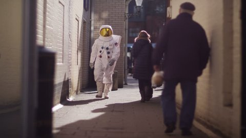 4K Funny astronaut walking through a city street on earth. Shot on RED Epic. UK - April, 2016