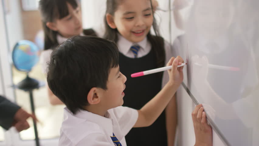 4K Happy school children in class writing on board with teacher UK - April, 2016