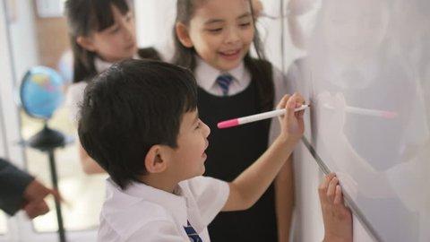 4K Happy school children in class writing on board with teacher UK - April, 2016