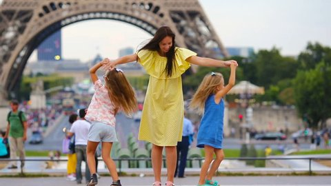 Happy family in Paris near Eiffel tower. French summer holidays, travel and people concept.