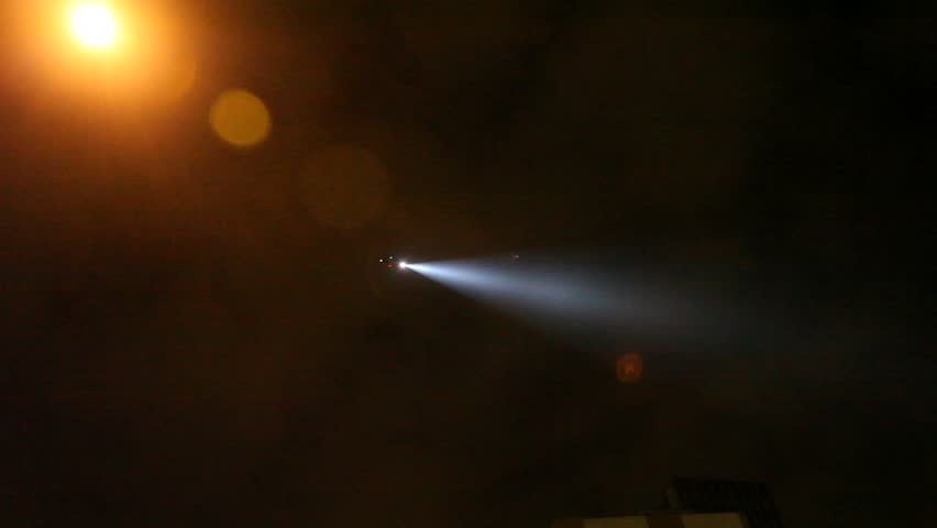 Military police helicopter shines searchlight down from night sky