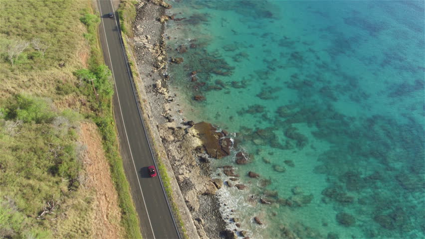 AERIAL: Red convertible car driving along beautiful coastal road in volcanic Hawaii island. Kauai landscape with great ocean road along the sea cliffs and pretty white sand beaches