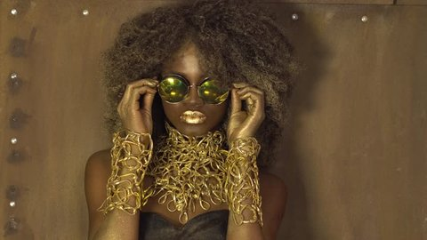Magic surreal golden african american female model in massive sunglasses with bright glitter makeup, glossy golden hairstyle and big red lips