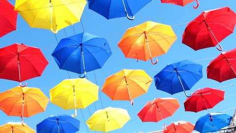 Multicolored umbrellas hanging over head on the street against the blue sky and swinging in the wind