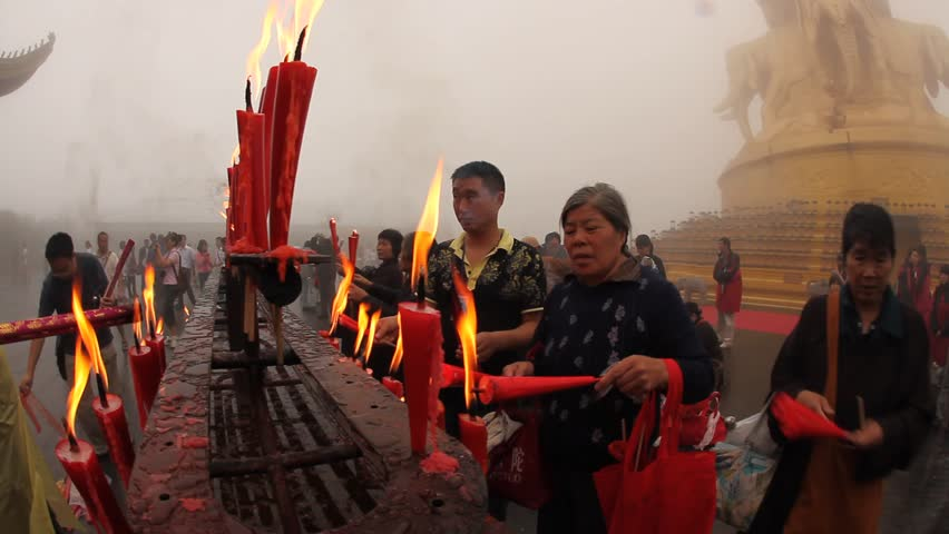 MOUNT EMEI, CHINA - JULY 22, 2009: People light candles and incense outside the Golden Summit Temple on July 22, 2009 on Mount Emei.