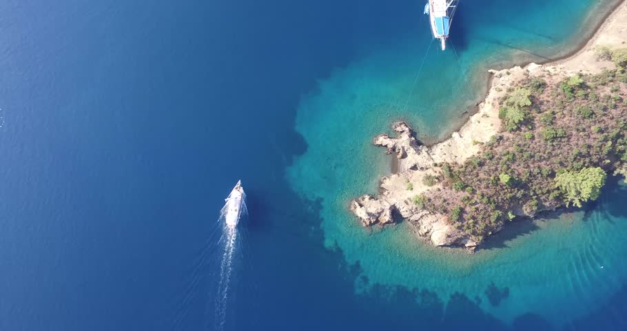 Gocek, Turkey, 2015. 4k aerial footage of the sailboat in the clear blue sea. Camera passes through the island.   Shutterstock HD Video #17109148